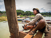 16 SEPTEMBER 2014 - SANGKHLA BURI, KANCHANABURI, THAILAND: A member of the Mon community uses a chain saw to shorten a pylon on the Mon Bridge. The 2800 foot long (850 meters) Saphan Mon (Mon Bridge) spans the Song Kalia River. It is reportedly second longest wooden bridge in the world. The bridge was severely damaged during heavy rainfall in July 2013 when its 230 foot middle section  (70 meters) collapsed during flooding. Officially known as Uttamanusorn Bridge, the bridge has been used by people in Sangkhla Buri (also known as Sangkhlaburi) for 20 years. The bridge was was conceived by Luang Pho Uttama, the late abbot of of Wat Wang Wiwekaram, and was built by hand by Mon refugees from Myanmar (then Burma). The wooden bridge is one of the leading tourist attractions in Kanchanaburi province. The loss of the bridge has hurt the economy of the Mon community opposite Sangkhla Buri. The repair has taken far longer than expected. Thai Prime Minister General Prayuth Chan-ocha ordered an engineer unit of the Royal Thai Army to help the local Mon population repair the bridge. Local people said they hope the bridge is repaired by the end November, which is when the tourist season starts.    PHOTO BY JACK KURTZ