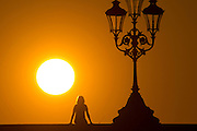UNITED KINGDOM, London: 20 April 2016 A commuter takes a picture as the sun sets on Putney Bridge this evening after another sunny day in the capital. Rick Findler / Story Picture Agency