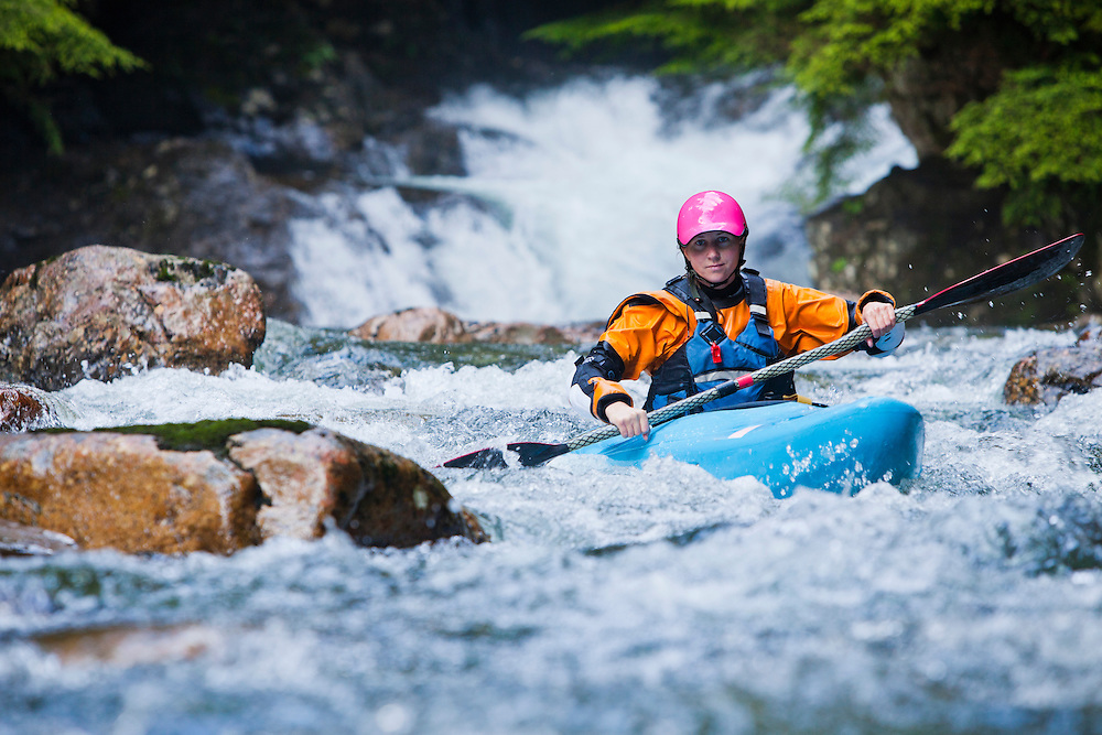 A woman kayaking down a series of small waterfalls, Snoqualmie River, Washington, USA.