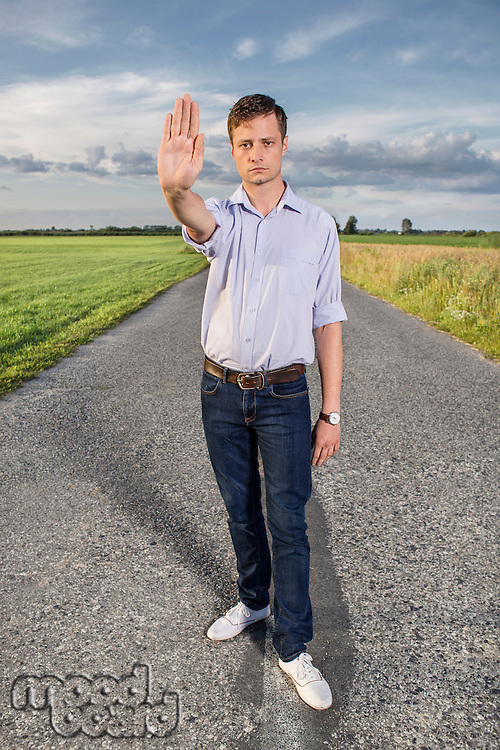 Full length portrait of senior young man showing stop gesture on country road