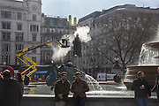 Winston Bogle of DBR Conservation maintenance cleaning statue in Trafalgar Sq. London. . 7 March 2018