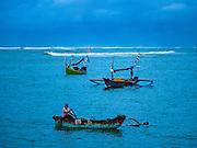 18 JULY 2016 - KUTA, BALI, INDONESIA:  A man rows his small boat back to shore at Pasar Ikan pantai Kedonganan, a fishing pier and market in Kuta, Bali. He works shuttling supplies and crewmen out to larger boats.   PHOTO BY JACK KURTZ