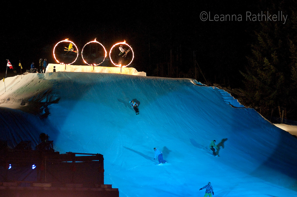 Skiers and snowboarders jump through flaming hoops in the Fire and Ice show during the 2010 Olympic Winter Games in Whistler, BC Canada.