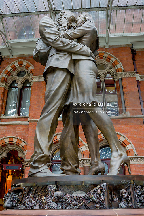 The artwork entitled The Meeting Place by British artist Paul Day stands in the main concourse at St. Pancras Station, on 10th April 2018, in London, England. The Meeting Place is a 9-metre high, 20-tonne bronze statue that stands at the south end of the upper level of St Pancras evoking the romance of travel through the depiction of a couple locked in an amorous embrace. The statue, is reported to have cost £1 million and was installed as the centrepiece of the refurbished station. The work, commissioned by London and Continental Railways, is modelled on the sculptor and his wife.