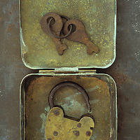 Old brass padlock lying in brass tin with its rusty keys lying in lid and resting on rusty metal sheet