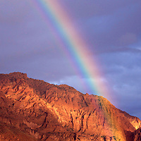 Rainbow appearing over the Navajo sandstone of the Red Mountains.  The nature landscape photograph was taken in Snow Canyon State Park of Utah, USA.