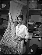 """21/05/1959<br /> 05/21/1959<br /> 21 May 1959<br /> Actress Dana Wynter selecting tweeds at Gaeltarra Eireann, Westland Row, Dublin. Miss Wynter was in Dublin for the premier of the film """"Shake Hands with the Devil"""". Picture shows her picking a piece of Round Tower Irish tweed at the showroom."""
