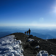 Climbers stand on the rim of the East Crater near the highest point of Mount Rainier as they look north during a summit of Mount Rainier on June 30, 2015. The iconic Pacific Northwest volcano is a popular challenge for mountaineers.  (Joshua Trujillo, seattlepi.com)