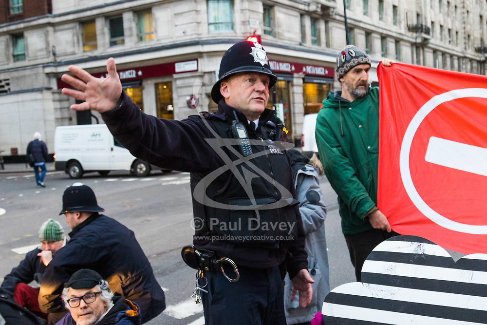 PICTURED: A police officer negotiates with anti pollution protesters. Demonstrators from the anti-pollution group Stop Killing Londoners cause traffic chaos for London commuters as they conduct a series of short roadblocks at Marble Arch stopping cars and buses from entering Oxford Street and Park Lane. Irate motorists accused them of creating more pollution than they were stopping, whilst the group said their objectives were long term. A leaflet handed out to motorists says the government is not doing enough to tackle the crisis costing 'taxpayers and the NHS £billions [sic] a year'. PLACE, January 29 2018. © Paul Davey