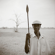 A bushman native keeps a watchful eye and a spear at hand while picking herbs and foraging for dinner, in case a Rino attacks. The Bushmen were displaced off thier land in South African jungle, and now must subsist in the desert of Botswana, Africa.