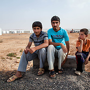 Boys from Damascus near the end of the day. People gather in the background to collect water from one of Village Three's wells. Azraq camp for Syrian refugees, Jordan, May 2014.