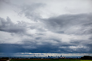 The skyline of Frankfurt am Main under a cloudy sky seen from a field in Oberursel, Stierstadt.