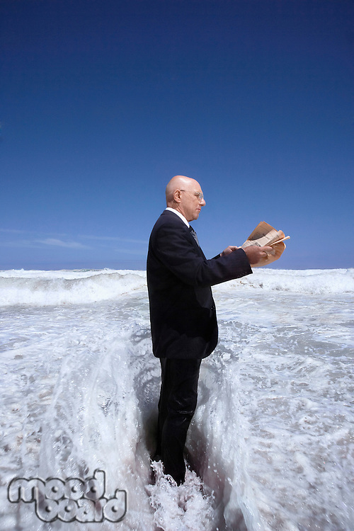 Businessman Standing in the Ocean Reading the Newspaper