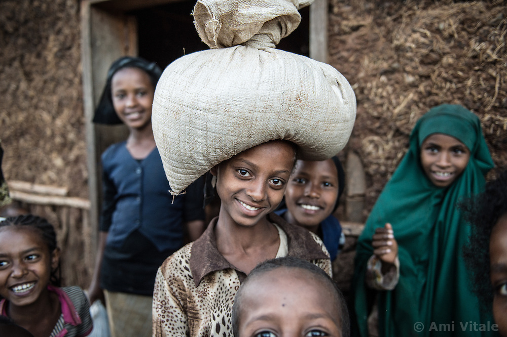 Sonia carries coffee beans to sell as her friend Samira stands on left in the village of Choche, in Jimmu Ethiopia. People beleive this is the place with coffee was discovered.
