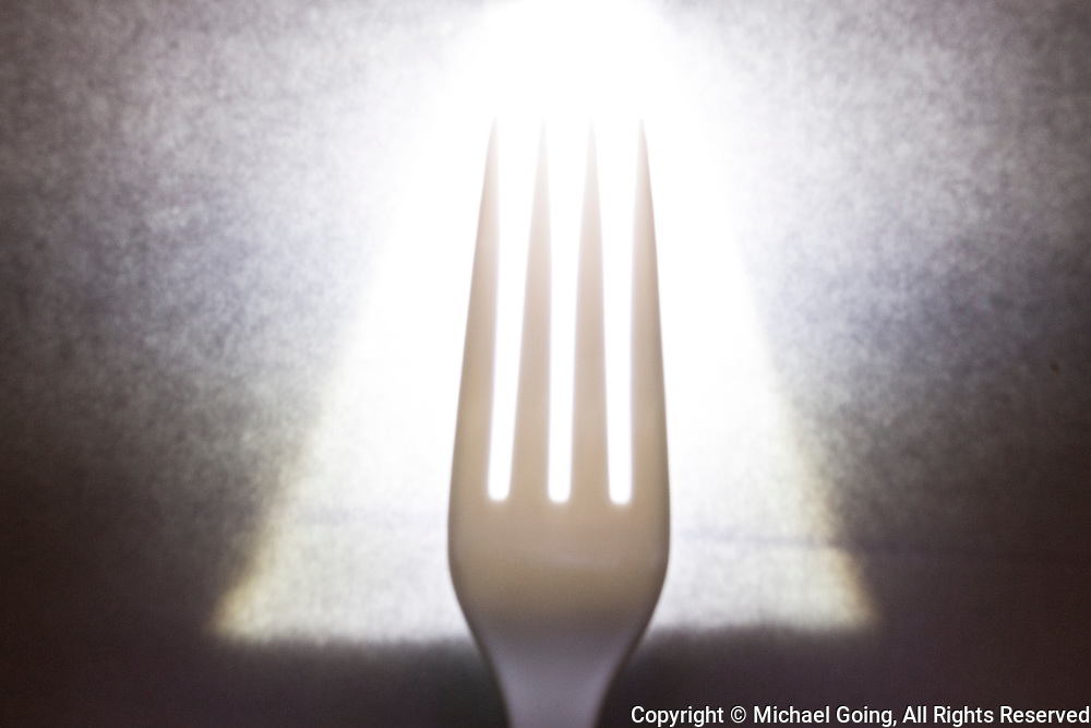 Glowing white plastic fork on napkin
