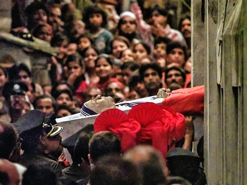 Mourners look on as Mother Teresa's casket is carried into Mother House where she was buried after her funeral Mass in the Netaji Indoor Stadium in Calcutta, Saturday, Sept. 13, 1997. (AP Photo/David Longstreath)