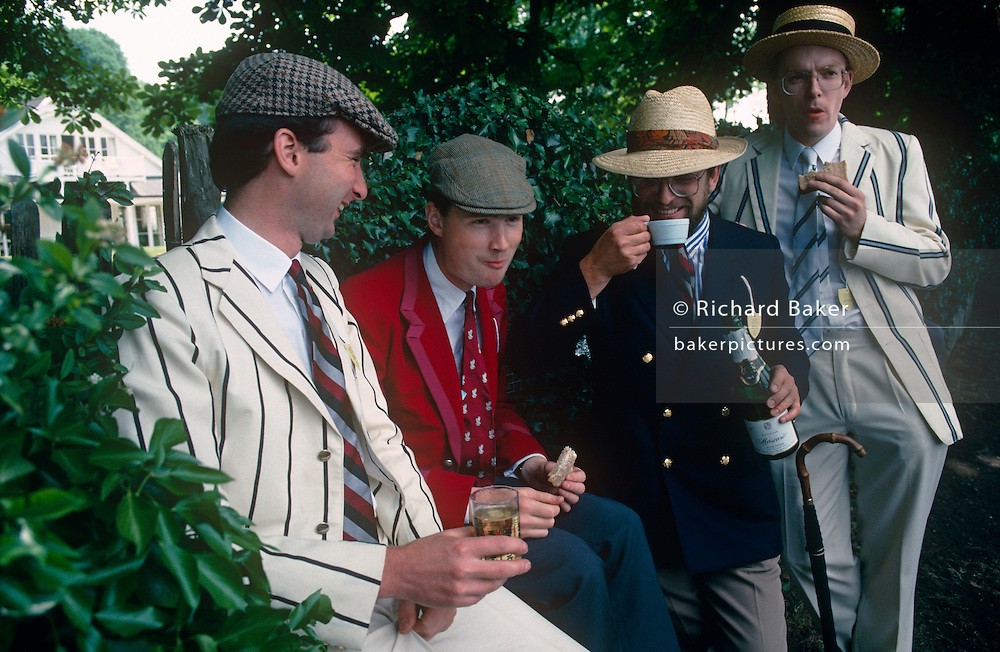 A group of four friends drink Champagne from glasses and plastic cups from beneath welcome shade during a particularly hot afternoon at the Henley Royal Regatta boat races, England. Dressed in quintessentially English blazers that denote their university and boat club, the four are in jovial spirits during this annual festival of high-society, serious rowing and general clowning around on the rural Thames. In 1829 a boat race challenge was held between teams representing the universities of Oxford and Cambridge. The venue chosen was a straight stretch of the Thames at the small town of Henley-on-Thames. Now held July and is one of the main dates on the sporting calendar and social season for the hoi polloi