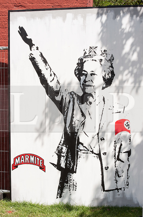 © Licensed to London News Pictures. 25/07/2015. Bristol, UK.  Art piece of HM the Queen by T.wat (correct) inspired by recent footage of the Queen as child prior to WW2 appearing to give a Nazi salute, at Upfest 2015, Europe's largest, free, street art & graffiti festival, attracting over 250 artists painting 28 venues throughout Bedminster & Southville, Bristol.  Talented artists travel from 25 countries and across the UK to paint live on 30,000sqft of surfaces in front of 25,000 visitors. There is also an affordable art sale, music stages and art workshops.  Photo credit : Simon Chapman/LNP