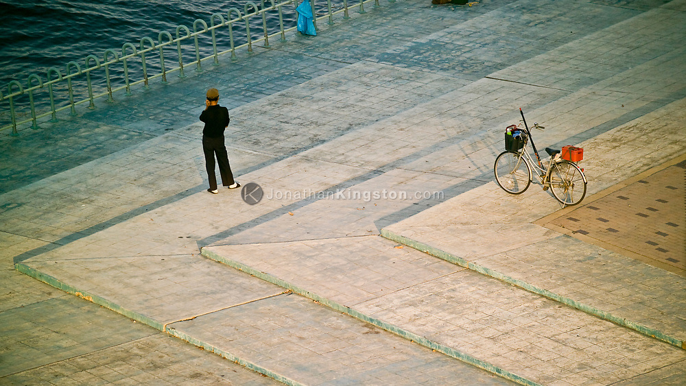 A lone man and bike at the waterfront near the port of Kobe, Kobe, Japan.  Kobe is a prominent port city in Japan with a population of about 1.4 million.  It is important as both a port and manufacturing center and is also famous for its Kobe beef and the Arima Onsen (hot springs).