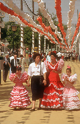 Spring Fair in Seville with women and young girls wearing Flamenco dresses; and garlands in background,