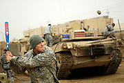 Before heading out on a mission, U.S. Army Spec. Timothy McClellan, Charlie Company, 1st Cavalry Division, 12th Infantry Regiment, plays a game of rock-baseball at the Army outpost in Kahn Bani Sahd, Iraq, on Feb. 6, 2007.