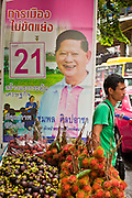 22 JUNE 2011 - BANGKOK, THAILAND: A fruit vendor waits for customers in front of a campaign poster on Silom Rd in Bangkok Wednesday. Yingluck Shinawatra, leader of the Pheua Thai party is running against  incumbent Prime Minister Abhisit Vejjajiva, head of the Democrat party. Yingluck is the youngest sister of exiled former Prime Minister Thaksin Shinawatra, deposed by a military coup in 2006. Yingluck is currently leading in opinion polls, running well ahead of the Democrat party, which in one form or another has ruled Thailand for most of the last 60 years.   Photo by Jack Kurtz