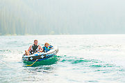 Father and son laugh and smile while tubbing on Red Fish Lake, Stanley, Idaho. MR