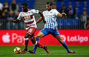MALAGA, SPAIN - DECEMBER 09:  Jeremie Boga of Granada CF (L) being fouled by Miguel Torres of Malaga CF (R) during La Liga match between Malaga CF and Granada CF at La Rosaleda Stadium December 9, 2016 in Malaga, Spain.  (Photo by Aitor Alcalde Colomer/Getty Images)