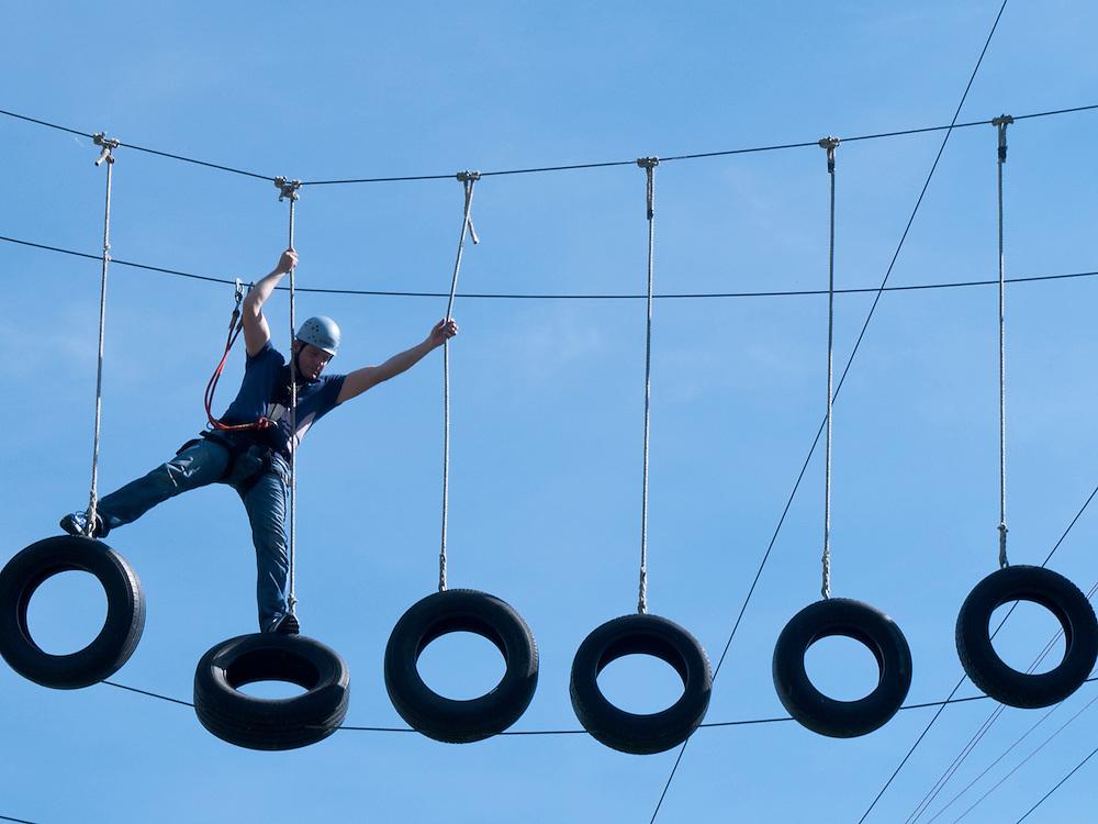 ein Mann klettert im Kletterpark - Hochseilgarten - Bad Oeynhausen über bewegliche Autoreifen    a man is climbing  over tires   