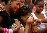 The family of  Iofemi Hightower consoles her sister Jasmine, 17, CENTER, at a makeshift memorial. Three college students were fatally shot execution style  in the playground behind an elementary school.
