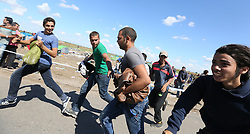 © London News Pictures. © London News Pictures. Migrants run to try and escape being contained by police close to the Hungarian and Serbian border town of Roszke, Hungary, September 7 2015. The UN's humanitarian agencies are on the verge of bankruptcy and unable to meet the basic needs of millions of people because of the size of the refugee crisis in the Middle East, Africa and Europe, senior figures within the UN have told the media.   Picture by Paul Hackett /LNP