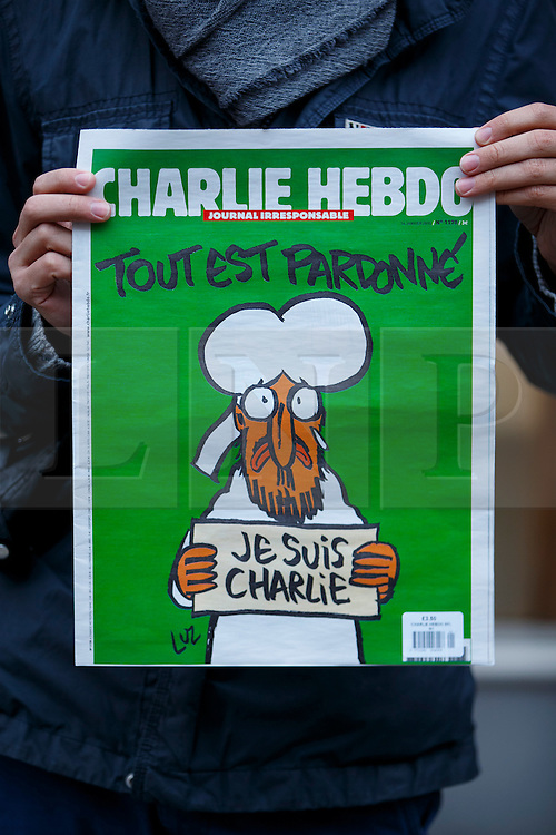 © Licensed to London News Pictures. 16/01/2015. LONDON, UK. A man posing with a copy of Charlie Hebdo's survival edition after buying it from 'La Page' book shop in London on Friday, 16 January 2015. Photo credit : Tolga Akmen/LNP