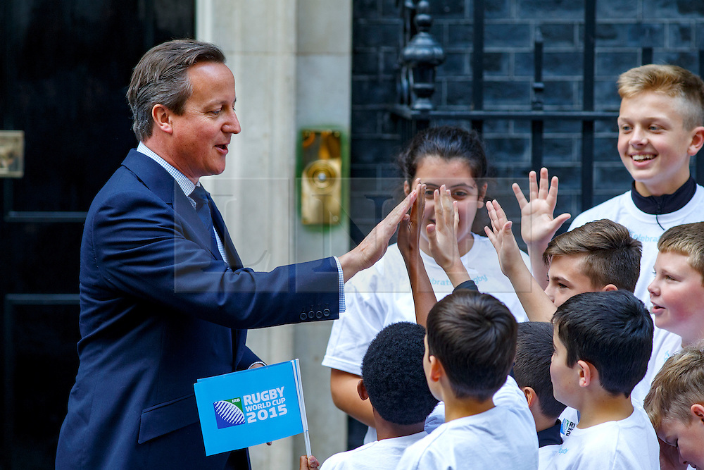 © Licensed to London News Pictures. 17/09/2015. London, UK. Prime Minister David Cameron high-fiving school children from the Rugby World Cup's host boroughs before welcoming the Webb Ellis Cup to Number 10 Downing Street, the day before the start of the Rugby World Cup on Thursday, 17 September 2015. Photo credit: Tolga Akmen/LNP