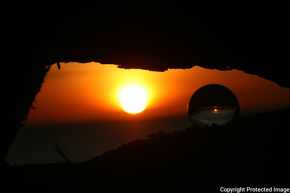 Crystal ball at sunrise, sunset under a deadfall of wood on Jekyll Island beach