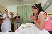ZHENGZHOU, CHINA - AUGUST 19: (CHINA OUT)<br /> <br /> A Girl Has A Big Leg<br /> <br />  Sun Jingjing sings a song for her doctor at Armed Police Corps Hospital of Henan on August 19, 2013 in Zhengzhou, Henan Province of China. 22-year-old Sun Jingjing, who was born with congenital angiolipoma in her right leg, underwent a leg-amputation surgery on July 23. And the hospital will offer her a prosthesis free of charge in three months. Sun Jingjing comes from a poor family in Baibi town of Anyang city, Henan province. She had never received any adequate treatment before, the circumference of her right leg was 85cm when her story was published by local media two months ago. Her father died by uremia 12 years ago, and her mother is suffering from esophageal cancer. They live on subsistence allowance from the local government.<br /> ©Exclusivepix
