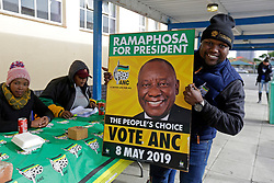 Wednesday 8th May 2019.<br /> JG Meiring High School, Goodwood Estate,<br /> Goodwood, Cape Town, <br /> Western Cape, <br /> South Africa.<br /> <br /> SOUTH AFRICAN GENERAL ELECTIONS 2019!<br /> <br /> SOUTH AFRICAN PROVINCIAL AND NATIONAL ELECTIONS 2019! <br /> <br /> An ANC political party member holds ups an ANC election poster with the face of South African President Cyril Ramaphosa on it as he and other representatives work on Election Day outside the voting station at JG Meiring High School, Goodwood Estate in Goodwood near Cape Town, Western Cape, South Africa.<br /> <br /> Registered South African Voters head to the various IEC (Independent Electoral Commission) Voting Stations where they are registered to vote as they cast their votes and take part in voting and other activities on Voting Day 8th May 2019 during the South African General Elections 2019. Voters from across the nation stood in queue's along with many others to vote in the Provincial and National Elections being held in South Africa on Wednesday 8th May 2019.   <br />  <br /> Copyright © Mark Wessels. All Rights Reserved. No Usage Without Permission.<br /> <br /> PICTURE: MARK WESSELS. 08/05/2019.<br /> +27 (0)61 547 2729.<br /> mark@sevenbang.com<br /> studioseven@mweb.co.za<br /> www.markwesselsphoto.com