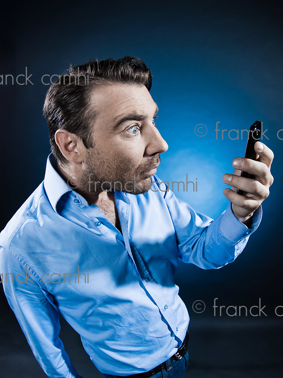 caucasian man unshaven looking at cellphone amazed portrait isolated studio on black background