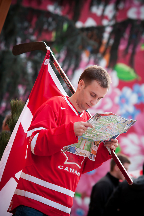 A hockey fan reads a map attempting to navigate a crowded downtown Vancouver.<br /> <br /> Tens of thousands of people in Vancouver took to the streets on Sunday 28th February 2010 to celebrate Canada's 3-2 overtime win over the United States for the gold medal in men's Olympic hockey...Traffic came to a halt in and around the downtown of the host city for the Winter Games following the dramatic finish to the match, which featured Sidney Crosby scoring to secure the victory on the final day of Olympic competition.