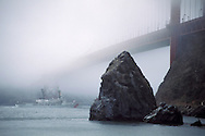 Coast Guard cutter Boutwell sailing under the fog covered Golden Gate Bridge, San Francisco Bay, California