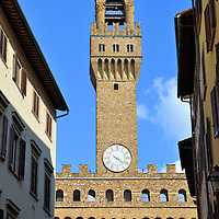 Palazzo Vecchio Tower from Via Vacchereccia in Florence, Italy<br /> This view of the classic Palazzo Vecchio is seen from a street called Via Vacchereccia. The 308 foot, rectangular tower casts a shifting shadow over Piazza della Signoria, Florence's central square. The first clock was installed in 1353. It was replaced in 1667 with this Giorgio Lederle Clock. Notice the timepiece only has one hand. The tower is named Torre d'Arnolfo after Arnolfo di Cambio. The 13th century architect also designed Santa Croce and the Duomo.