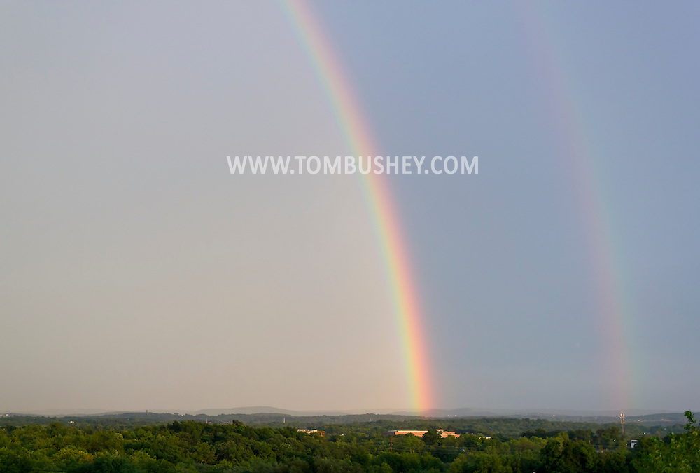 Scotchtown, New York - Double rainbows arc across the sky after a thunderstorm on Aug. 5, 2012. The secondary and dimmer rainbow is on the right side of the frame and has its colors reversed from the primary rainbow.