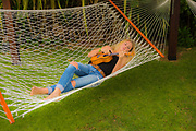 14 year old teenage girl playing the ukulele lying on a hammock people ****Model Release available
