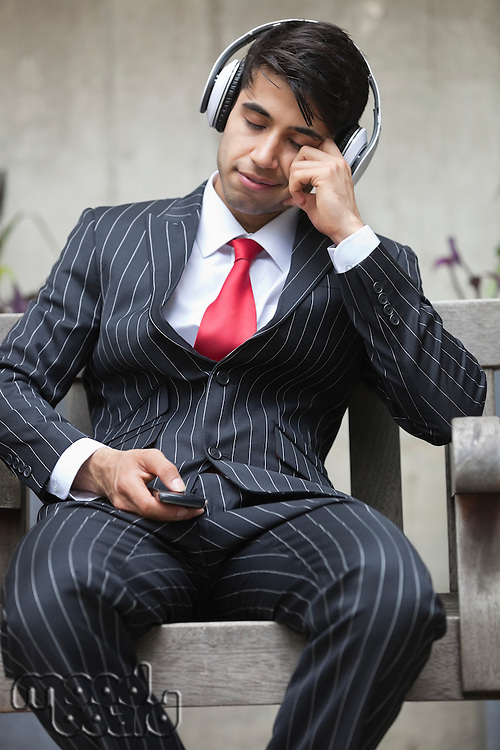 Young Indian businessman with eyes closed listening music on headphones