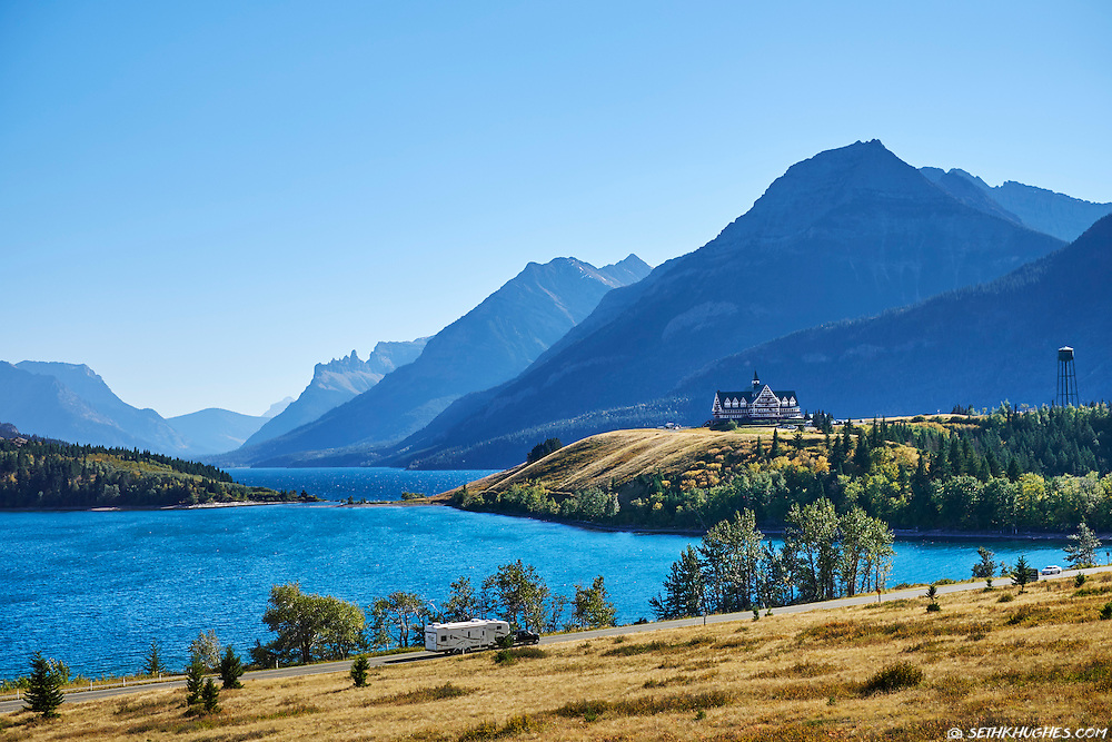 An RV drives down the road entering the picturesque setting of Waterton Lakes National Park, Alberta, Canada.