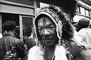A black man, wearing face-paint and an Indian headress, Notting Hill, Carnival, London, UK, 1983.