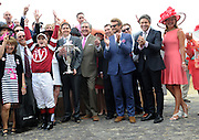 Actor and Longines Ambassador of Elegance Simon Baker, third right, Jennifer Judkins, right, and Juan-Carlos Capelli, second right, both of Longines, applaud jockey Rosie Napravnik after she rode Untapable to win the Kentucky Oaks for the second time in three years on Longines Kentucky Oaks Day, Friday, May 2, 2014, in Louisville, Ky.  Longines, the Swiss watch manufacturer known for its luxury timepieces, is the Official Watch and Timekeeper of the 140th annual Kentucky Derby. (Photo by Diane Bondareff/Invision for Longines/AP Images)