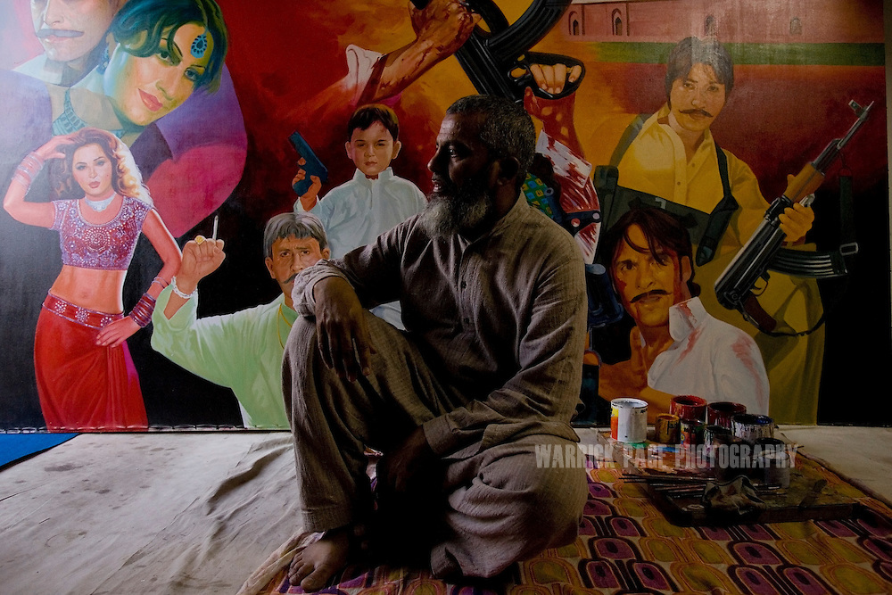 LAHORE, PAKISTAN - MAY 11: Billboard painter, Muhammed Ajmal, sits in front of a work-in-progress  Friday, May 11, 2007, in Lahore, Pakistan. Billboard painters have had to cut their prices in half due to few Lollywood productions and the use of soft-porn posters to entice patrons. As thawing relations between Pakistan and India lead them closer to regional stability, Pakistan's film industry takes another hit as Bollywood films dominate an already floundering institution, as the Pakistani government eases a 43-year-old ban on screening Indian films and audiences are drawn to their neighbours silver-screen theatrics. Once a thriving film industry in the chaotic and colourful city of Lahore, Pakistan's answer to Bollywood - Lollywood - is now a shadow of its former self. Two decades ago 11 studios averaged a collective 100+ films per year as cinemagoers filled more than 1000 theatres across the country. Today, only one functioning studio struggles to produce a single film for the country's 200 decaying theatres. (Photo by Warrick Page)