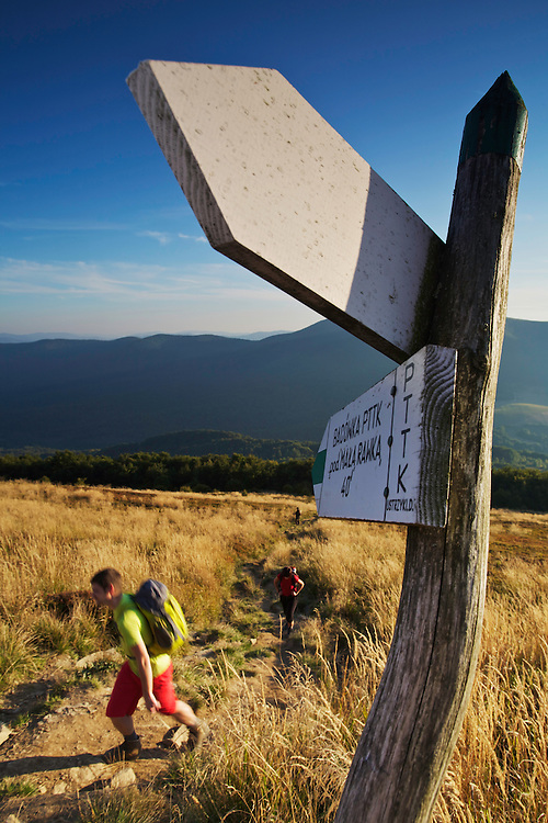Signposts pointing to the highest mountain in Bieszczady National Park,  Ppolonina Carynska (1234 m) and hikers. Ustrzyki Górne, Poland.