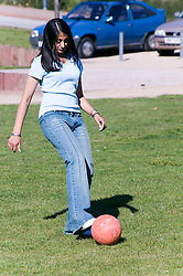 Teenaged girl kicking a football around the park,