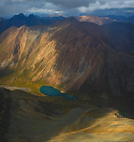 A high altitude pristine mountain lake is sheltered by the towering peaks of the endless mountains of the Yukon's Peel Watershed,spot lit by the afternoon sun breaking through stormy skies. What an amazing flight this was!